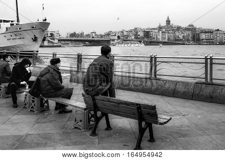 Istanbul Turkey - February 21 2013: Istanbul view. Eminonu pier Galata bridge and Galata tower. People are resting on the bench.