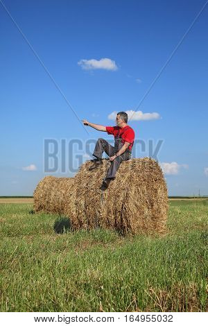 Farmer And Bale Of Hay In Field