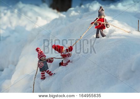 scene to rescue toy men who fell from a snowy mountain a girl pulls a rope with two boys