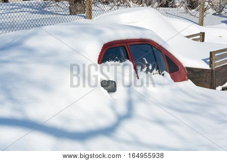 Car buried under deep snow after a snow storm. Snowdrift