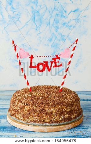 Festive cake with a topper Love on a blue background. Honey cake with walnuts and grated chocolate