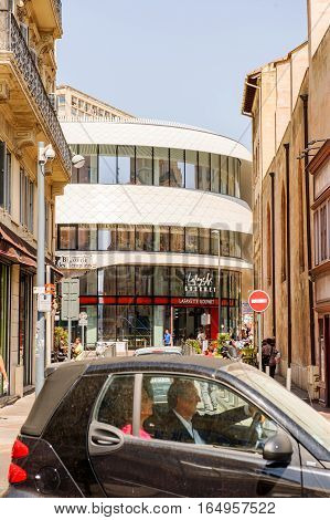 MARSEILLE FRANCE - JUL 18 2014: Senior couple driving car with Lafayette Gourmet supermarket in the background with people on streets and tourist commuting in cars on a warm summer day in French city of Aix-En-Provence