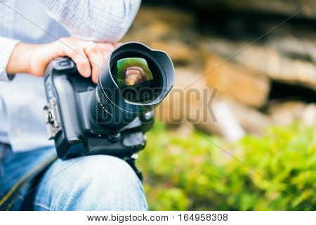 a photographer is holding his big dslr camera.