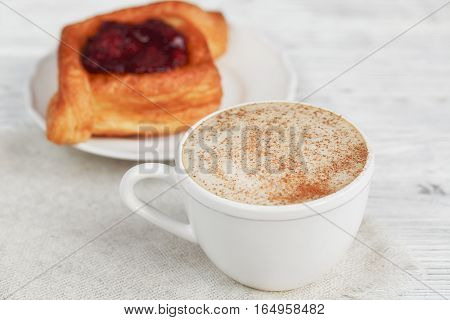 Fruit dessert and coffee on a white wooden table