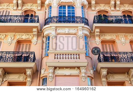 A pink facade with windows, shutters, balconies and wrought iron balusters in Nice on the French Riviera