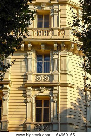 Yellow facade with stucco, balcony and windows in Nice