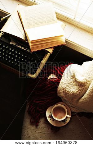 Typewriter with open book by the windowsill. Cozy blanket and chair with antique teacup on it