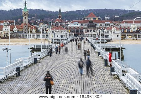 People walking on a pier (Molo) in Sopot city, Poland. Built in 1827 with 511m long it is the longest wooden pier in Europe (Long exposure, non recognizable people)
