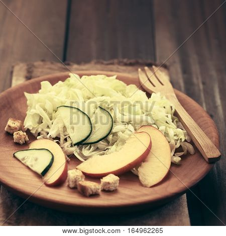 Fresh nectarine cucumber and iceberg lettuce salad on wooden plate with homemade croutons on the side photographed with natural light (Selective Focus Focus on the cucumber slices in the middle of the plate) (Digitally Altered: Toned Image)