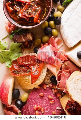 Typical traditional spanish smoked salamis and jamon served on rustic cutting board with sliced brie cheese jerking tomato and olives on rustic wooden chopping board over rustic backdrop top view