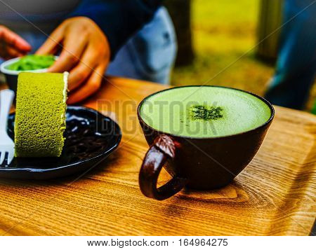 Green tea roll cake and green tea latte coffee in green tea shop at Osulloc tea museum Jeju island South Korea.