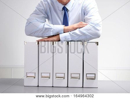 Businessman leaning on a folder in the office .