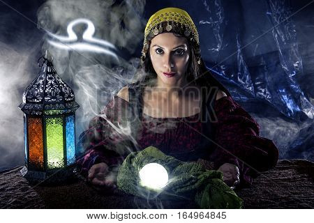 Psychic or fortune teller with crystal ball and horoscope zodiac sign of Libra