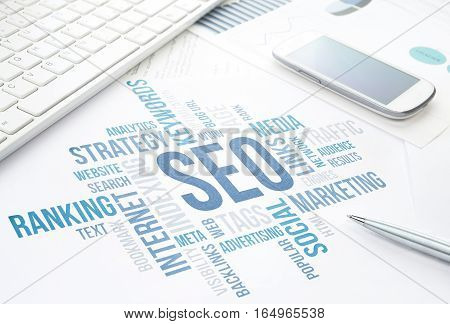 Seo business search engine optimization concept cloud chart. Print document keyboard pen and smartphone. Blue toned.