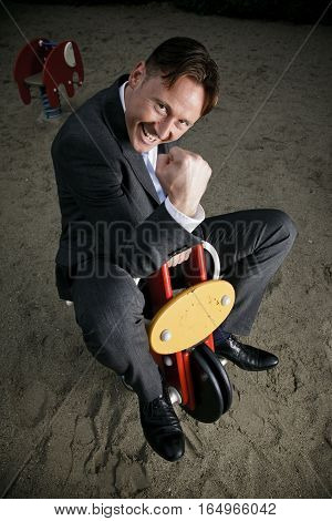 businessman on a playground, aiming for success.