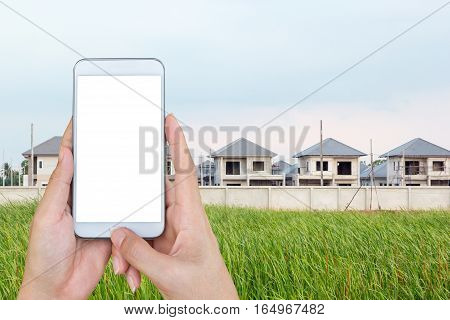 Hand holding and touch screen smart phone looking for a new houses in suburb.