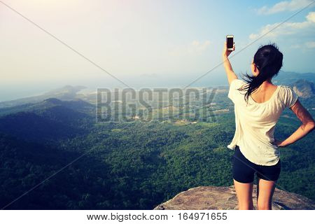 young asian woman taking photo with smart phone at mountain peak cliff