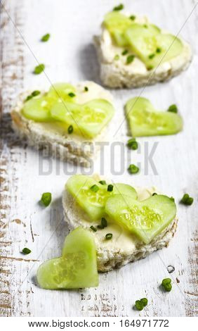Cucumber sandwiches in heart shaped on wooden background