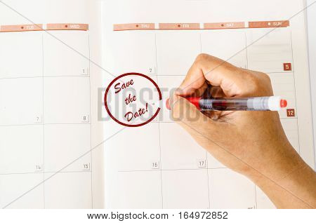 Red circle.Mark on the calendar with words Save the date written on a calendar to remind you an important appointment