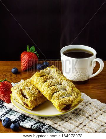Danish rolls with starwberry blueberry and coffee for breakfast