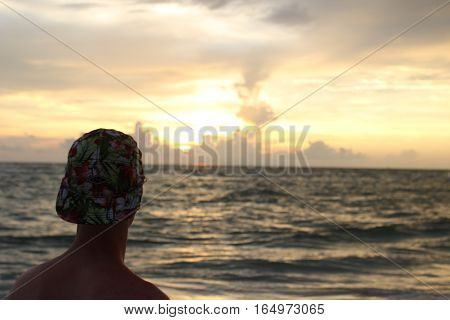 A young man watches as the sun sets over the ocean.