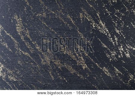 Black background with golden sparkling sequins. Dark surface strewn with gold crystals.