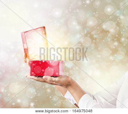 Hands holding and pening a red gift box with magical special effects lights.