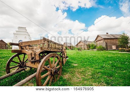 Old wooden cart standing on a green grass of the countryside in the background Slavonic huts
