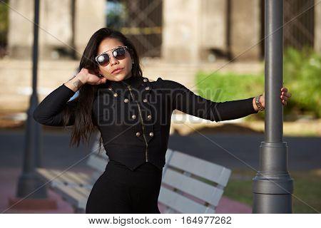 Glamur latina girl in gold sunglasses posing on street