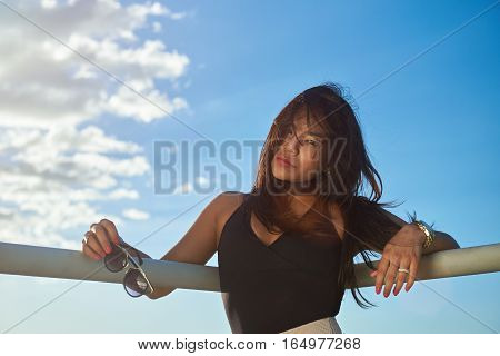 Portrait of latina woman holding sunglasses on blue sky background
