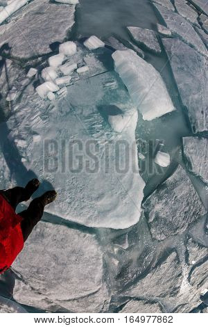 top view of a human foot on the ice is covered with cracks and hummocks.