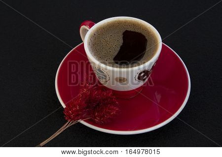 Red cup of coffee with red dry flowers on black background top view