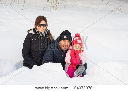 Happy motherfather and daughter posing in snow