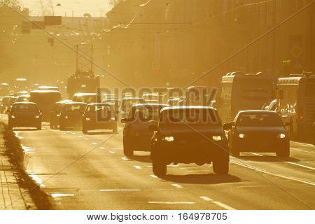 The heavy traffic and urban transport on the highway.