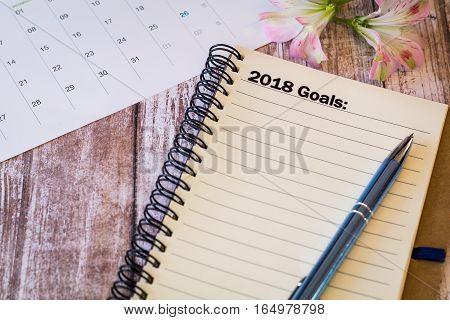 2018 Goals motivational business concept on notebook and calendar on wooden board