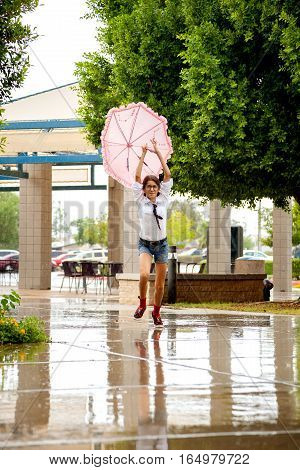 A girl dressed like a nerd with a small tie and big glasses runs through the rain holding a pink umbrella behind her over her head.