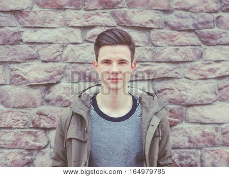 Young beautiful man on the city brick wall background