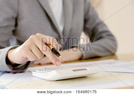 Close up of female accountant or banker making calculations. Savings finances and economy concept