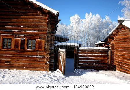 Traditional Russian wooden architecture in Siberia. House of logs with blind window shutters and fence. View winter. Taltsy. Irkutsk. Russia.