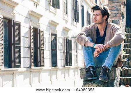 City young handsome man. Urban sitting model. Building windows. A beautiful young man sitting on a ledge