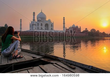 Woman watching sunset over Taj Mahal from a boat Agra India. It was build in 1632 by Emperor Shah Jahan as a memorial for his second wife Mumtaz Mahal.