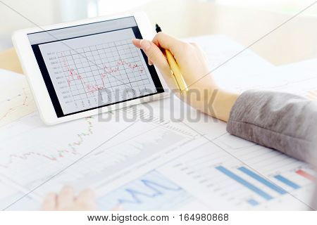 Close up hand holding digital tablet with analyzing graph planing business success