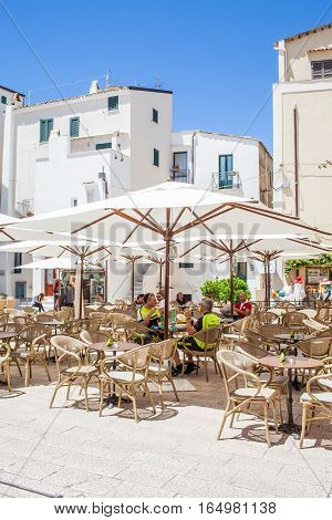 SPERLONGA LAZIO ITALY - MAY 30 2016: Tourists drinking coffee in the main square of the old historical city in a very picturesque ambient with white-painted houses reminding a bit some Greek islands.