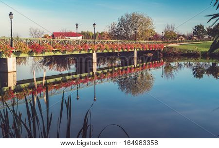 Bridge with flowers reflecting in lake .