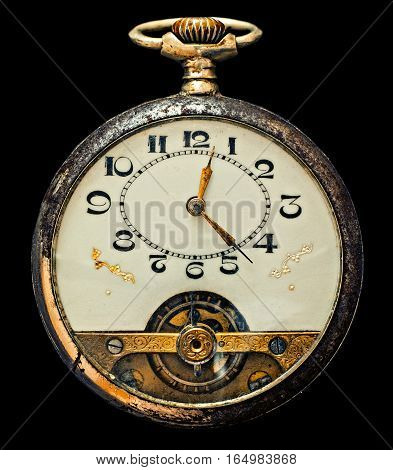 Antique pocket watch isolated on a black background, top view.
