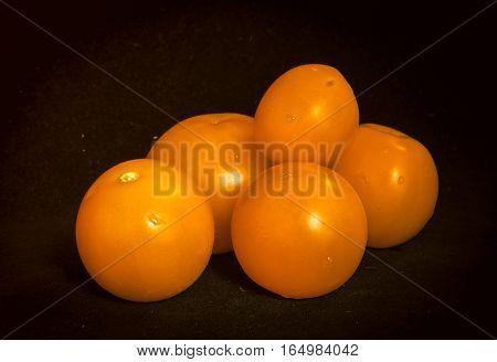 Bunch of ripe tomatoes orange on a black velvet background.