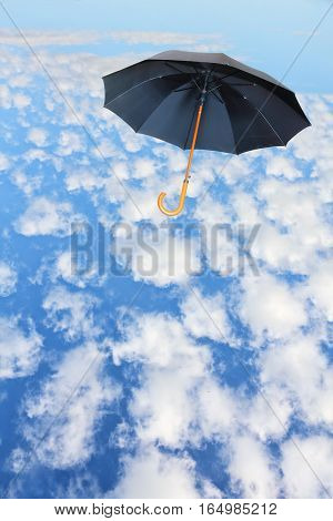 Black umbrella flies in sky against of white clouds.Mary Poppins Umbrella.Wind of change concept.