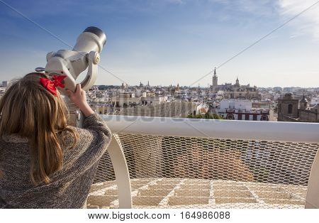 Little girl with telescope pointing to old town landmarks over Metropol Parasol roof Seville Spain