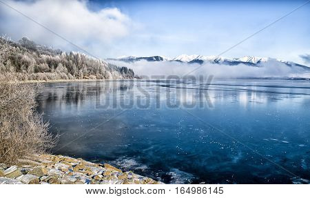 Lake Liptovska Mara Slovakia covered in ice.on a quiet winter days. Backround of snow covered mountains peaks.