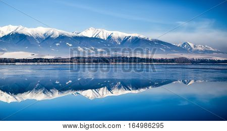 Rreflection on lake Liptovska Mara Slovakia covered in ice.on a quiet winter days. Backround of West an High Tatras mountains Slovakia. Beautiful landscape